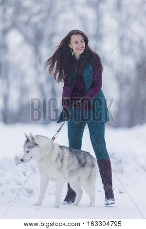 Portrait of Smiling and Happy Caucasian Woman Airing Her Husky Dog Outdoors in Forest.Vertical Image