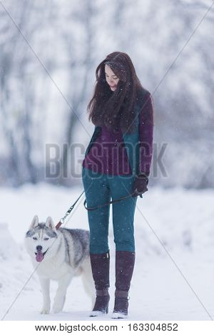 Portrait of Smiling and Happy Caucasian Woman Airing Her Husky Dog Outdoors in Forest.Vertical Shot