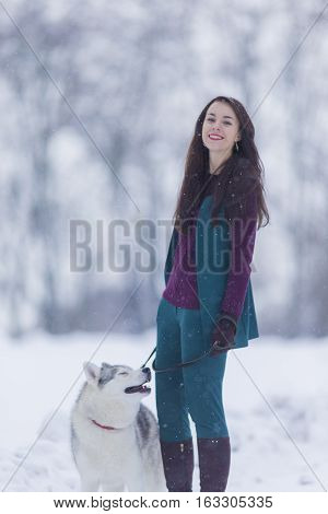 Lovely Couple. Portrait of Smiling and Happy Caucasian Woman Airing Her Husky Dog Outdoors in Forest.Vertical Image Orientation