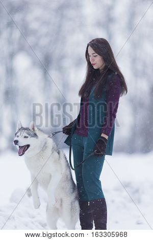 Caucasian Brunette Woman Keeping Her Husky Dog on a Short Leash During a Stroll in Winter Time Outside.Vertical Image