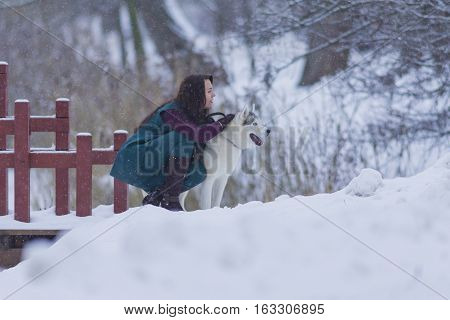 Portrait of Pretty Tranquil Caucasian Brunette With Her Husky Dog during a Stroll in Winter.Horizontal Image