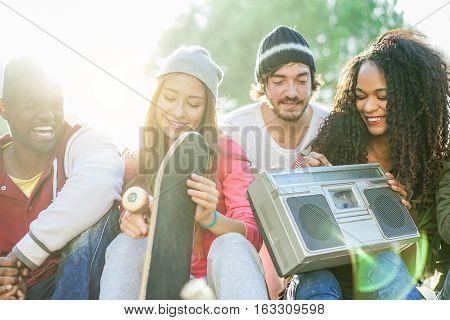 Happy multi ethnic friends having fun and listening music in skate park with back sun light - Young people chilling and socializing in London - Friendship concept - Focus on girls - Warm filter