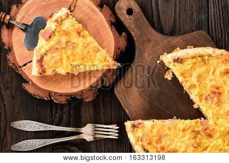 Homemade quiche with leek, ham and cheese on wooden background.