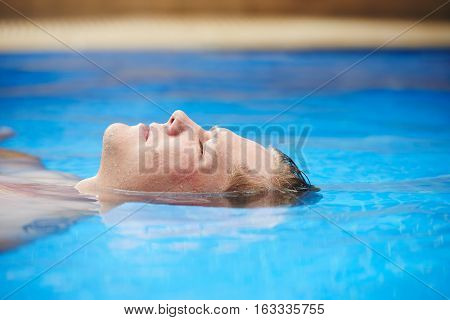 Face of man floating in pool with his eyes closed