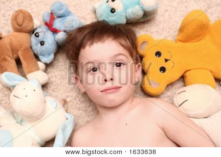The Boy Lays Among Soft Toys