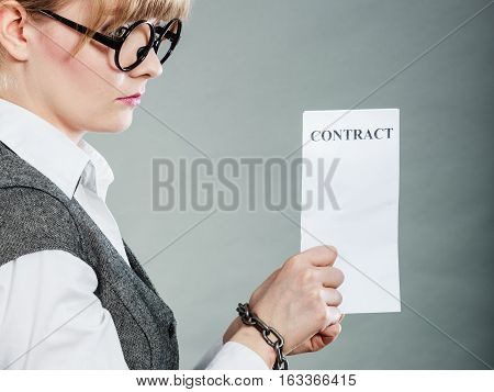 Business concept. Serious businesswoman with chained hands holding contract