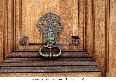 Beautiful detail in heavy wood door and metal hardware, at entrance of home.