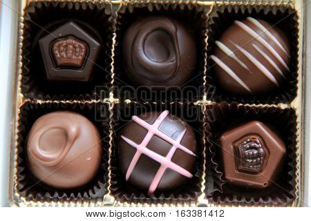 Box of six chocolates, each tempting in dark,white or milk chocolate with designs on top.