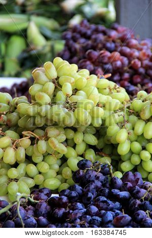 Vertical image of green,red and purple grapes on sale at local market