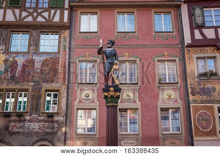 Statue of a warrior on a background of houses decorated with frescoes in Stein am Rhein, Switzerland