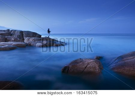 long exposure of blue sea scape at morning light with man fishing on rock