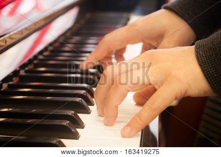 Woman playing on piano keyboard, stock photo