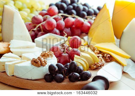 variation of selective cheese on wooden board with fruits
