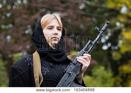 Woman In Muslim Dress With Arms In Autumn Day