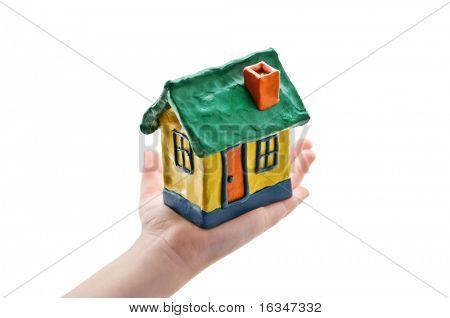 Casa en la mano del niño aislado