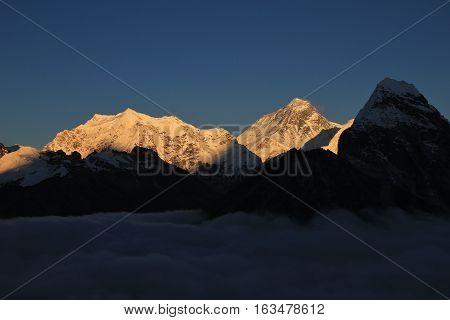 Autumn scene in the Himalayas. Illuminated Mt Everest and sea of fog.