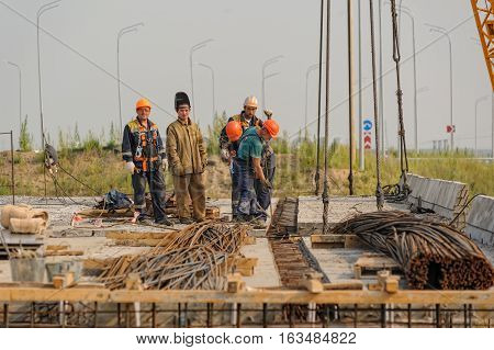 Tyumen, Russia - July 31, 2013: JSC Mostostroy-11. Bridge construction for outcome of the Tobolsk path and Bypass road round Tyumen. Workers on bridge construction. Mounting of bridge span