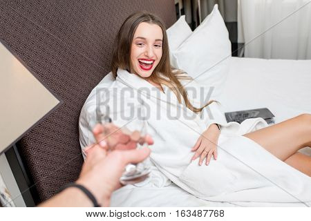 Happy woman in bathrobe taking glass of water lying on the bed