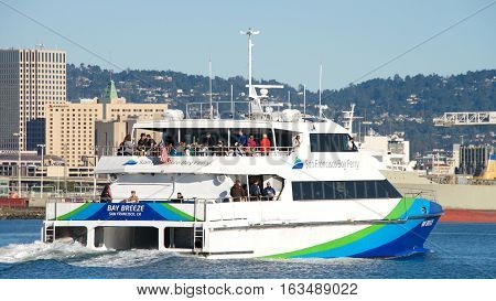 Oakland CA - December 28 2016: San Francisco Bay Ferry BAY BREEZE passing the Port of Oakland. The Ferry provides weekday weekend holiday and seasonal service to 8 terminal locations around the bay.