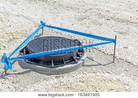Three metal sticks with blue tape that is surrounding area around the fresh assembled new manhole with metal cover.