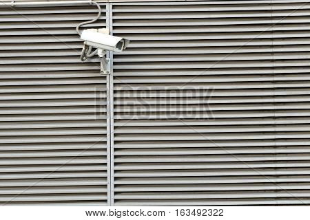 Security camera on modern a building horizontal stripes wall
