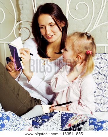 portrait of mother and daughter laying in bed  reading and writing, lifestyle people concept close up