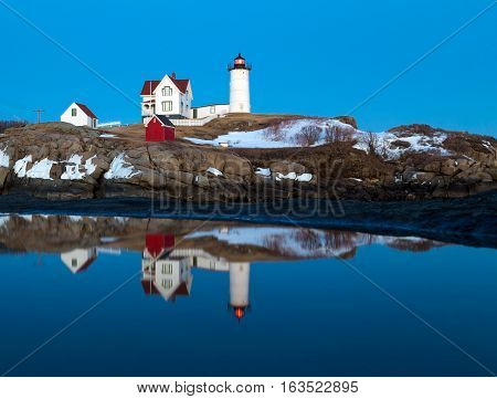 This is an image of the Nubble Light in York Maine taken during a Winter twilight. A reflection of the lighthouse can be seen in a puddle. The lighthouse is also known as the Cape Neddick Light.