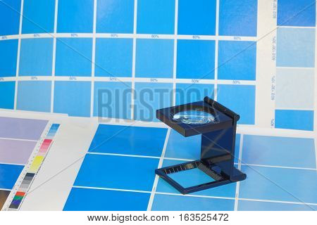 Magnifying glass standing on a leaf of the cyan test print in a pre-press workshop. Very short depth of focus