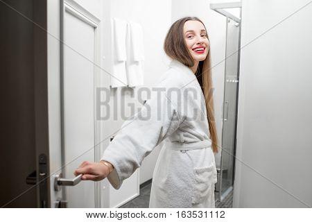 Portrait of happy woman in bathrobe in the bathroom