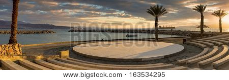 Colorful sunset at the Red Sea; panoramic view from stone amphitheater on central beach of Eilat - famous resort and recreational city in Israel