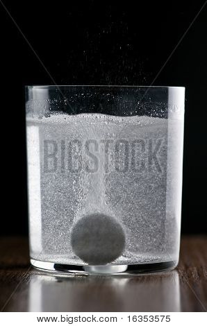 aspirin tablet in glass of water