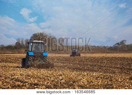 Two large blue tractor plow plowed land after harvesting the maize crop on a sunny clear autumn day.