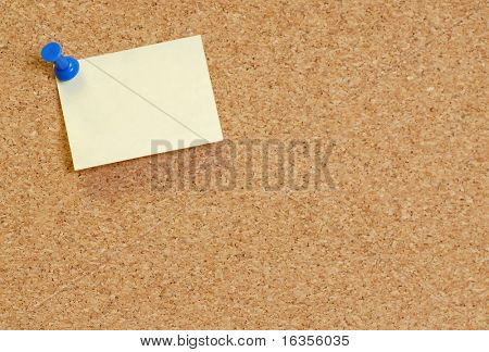 cork board with blank note attached with thumb pin