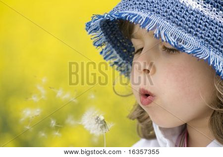 Girl blowing dandelion