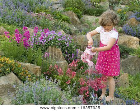Cute girl watering flower in the garden