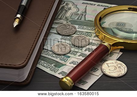 Notebook Russian Banknotes And Coins, Magnifying Glass Lying On A Dark Wooden Table. Business Still