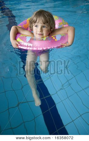 Little girl with inner tube floating on swimming pool