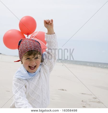 Cute girl playing with balloons on the beach