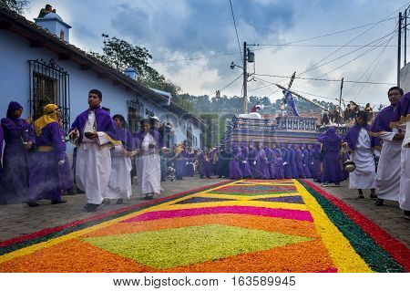 Antigua Guatemala - April 16 2014: Man wearing purple and white robes carrying a float (anda) during the Easter celebrations in the Holy Week in Antigua Guatemala.