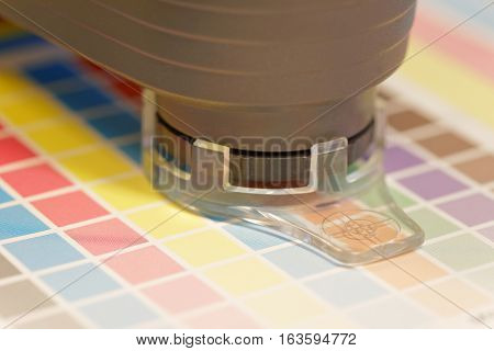 Closeup of spectrometer used for proofing on a leaf of the cmyk test print in a pre-press workshop