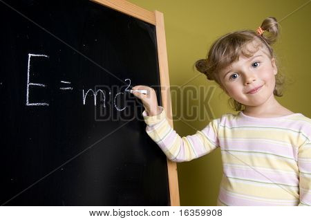 Cute girl standing in front of blackboard. Holding chalk. Smiling and looking at camera