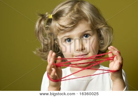 Little girl playing cats cradle game