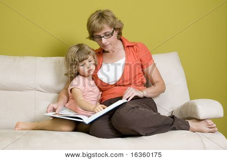 Mother and daughter reading book on sofa