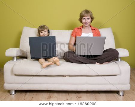 Mother and daughter working at laptops
