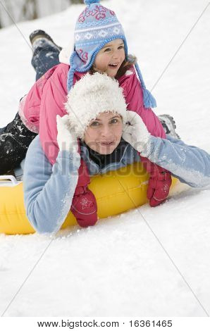 Mother and daughter sliding downhill on tube