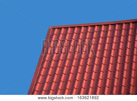 Top of country house roof covered with red metal tile isolated on blue closeup