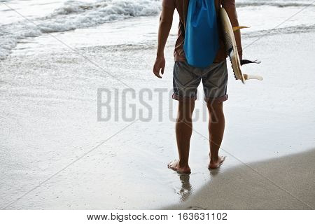 Portrait Of Lower Half Of Surfer With His Board Standing On Seashore With Copy Space For Your Advert