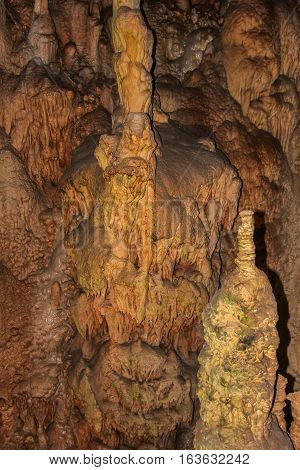 Underground cave with stalactites and stalagmites. Limestone karst formation on the walls of caves.