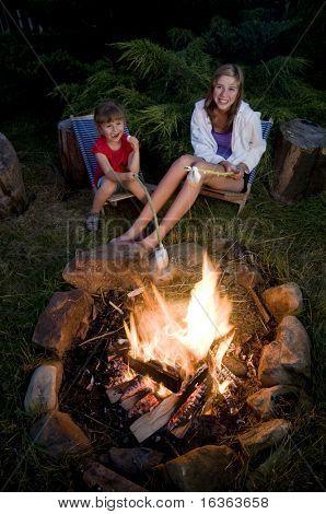 Two girls roasting marshmallows