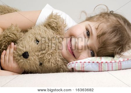 Little girl with teddy bear on sofa